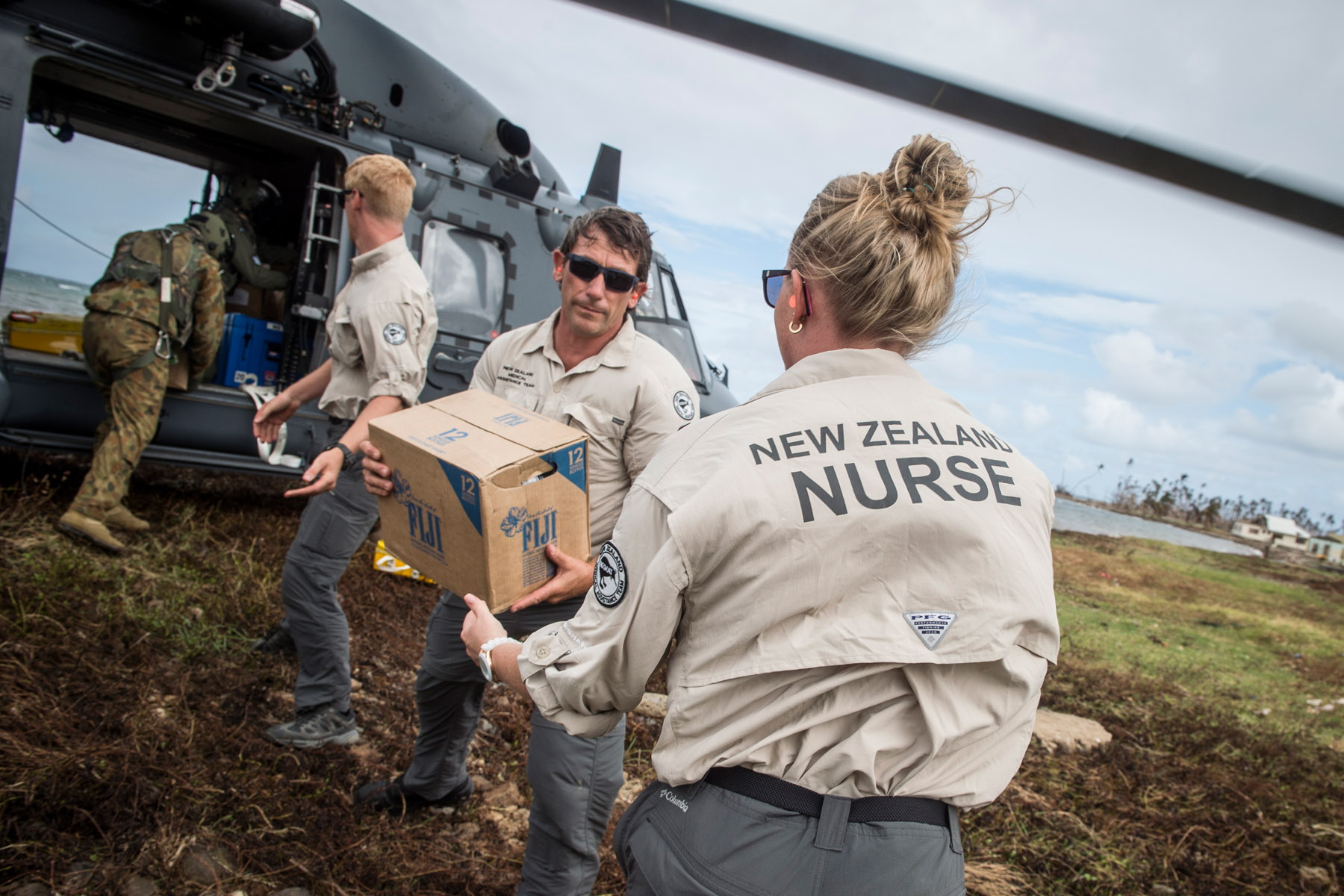 Members of NZ Medical Assistance Team help unload aid and equipment in Nasau, Koro Island following Tropical Cyclone Winston (image: NZDF / NZ MFAT)