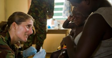 A New Zealand Army officer treats a child at the patrol's temporary medical clinic in Mbarama village, Solomon Islands (New Zealand Defence Force/Flickr/CC BY-2.0)