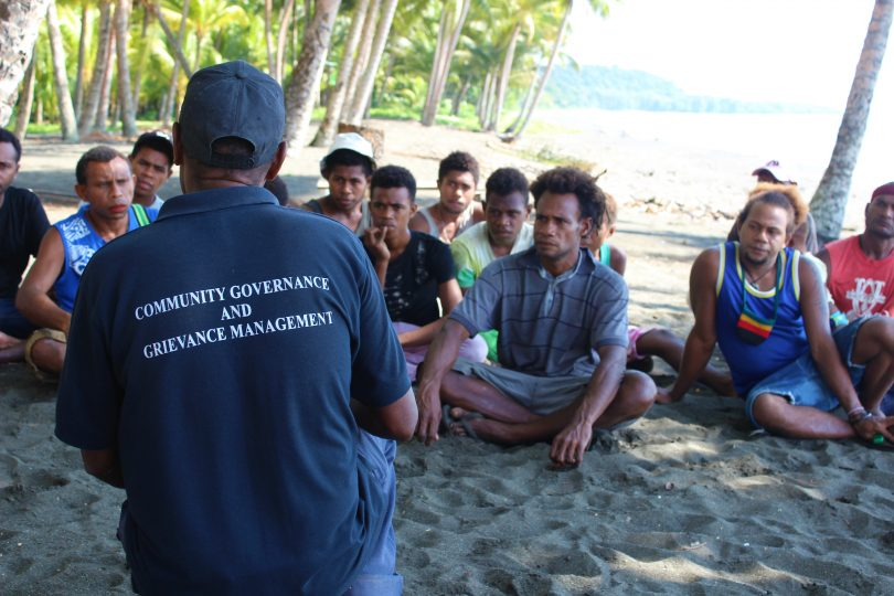 Community Officer Daniel Danegu speaks with young men in Kokana village, Makira, Solomon Islands (Credit: World Bank)